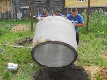 Установка бетонного кольца при копке колодца