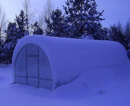 Укрытая снегом теплица