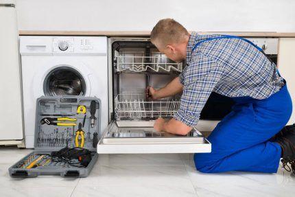 Мастер ремонтирует посудомойку