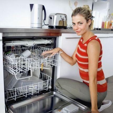 Девушка укладывает посуду в посудомойку