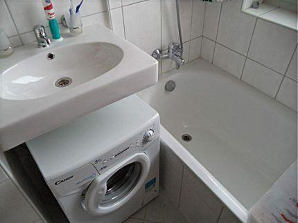 Белая навесная раковина над стиральной машиной