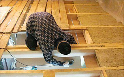 Мастер утепляет потолок