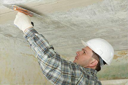 Мастер выравнивает потолок