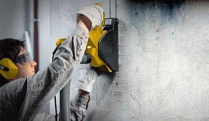 Рабочий пробивает штробы в стене