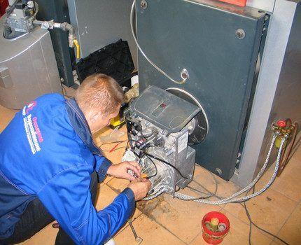 Мастер ремонтирует газовый котел