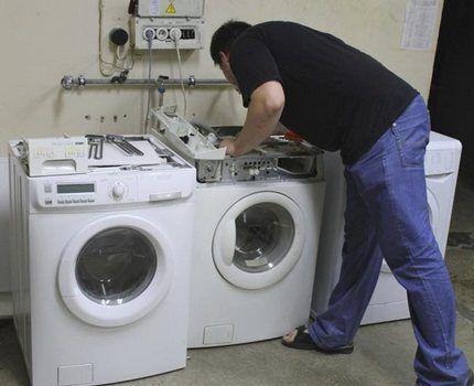 Мастер осматривает стиральные машины