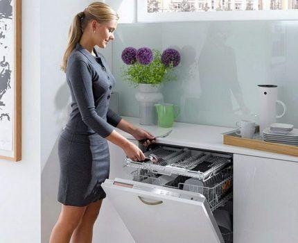 Девушка открывает посудомоечную машину