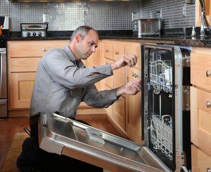 Мастер осматривает посудомоечную машину