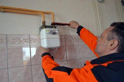 Техник монтирует газовый счетчик
