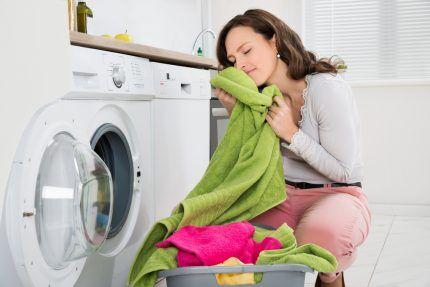 Женщина вынимает белье из стиралки