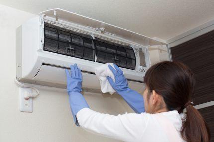 Женщина чистит настенную сплит-систему