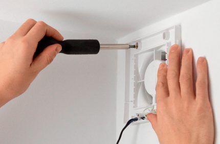 Мастер прикручивает вытяжной вентилятор отверткой