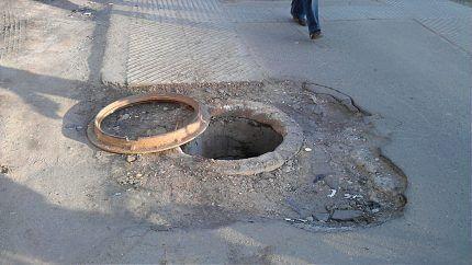 Открытый канализационный колодец на дороге