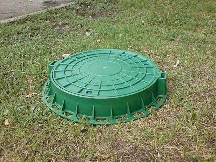 Люк из зеленого пластика на земле