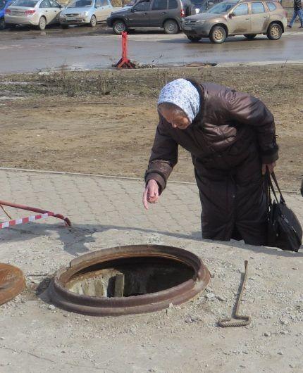 Пожилая женщина смотрит в канализационный колодец