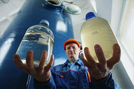 Мужчина держит в руках бутылки с реагентами