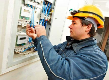 Электрик меняет счетчик