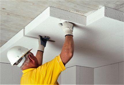 Мастер утепляет потолок плитами