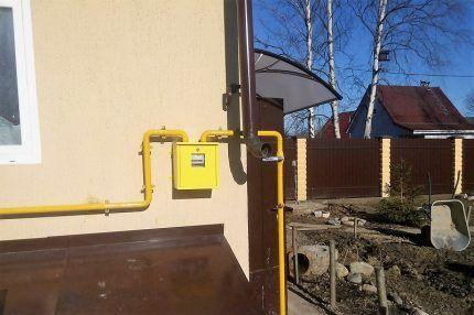 Прибор учета газа на стене дома