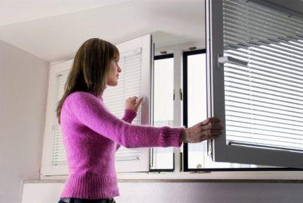 Женщина открыла окно на проветривание