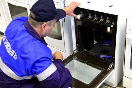 Специалист Горгаза проверяет исправность духовки