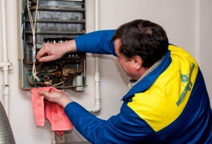 Специалист службы газа проверяет котел
