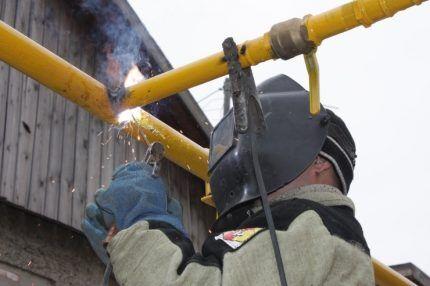 Сварщик режет трубу
