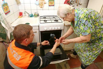 Работник газовой службы проверяет плиту