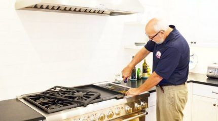 Специалист чинит газовую плиту