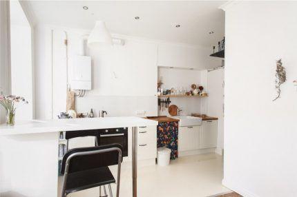 Белая колонка на фоне белой кухни