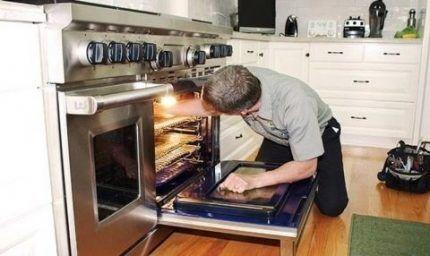 Мастер ремонтирует духовку