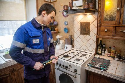 Газовщик проводит ремонт плиты