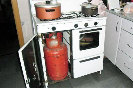 Газовый баллон в специальном отделении плиты