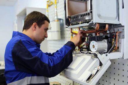 Представитель газовой службы ремонтирует котел