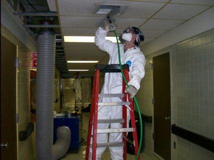 Мастер проводит дезинфекцию воздуховодов