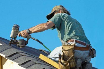 Монтажник на крыше дома