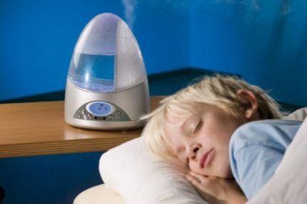 Ребенок спит возле увлажнителя