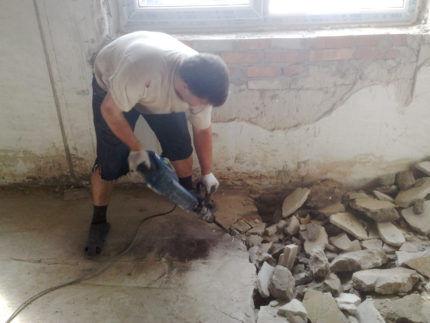 Мужчина перфоратором демонтирует стяжку пола