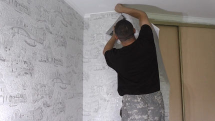 Мужчина проводит облицовку стен флизелиновыми обоями